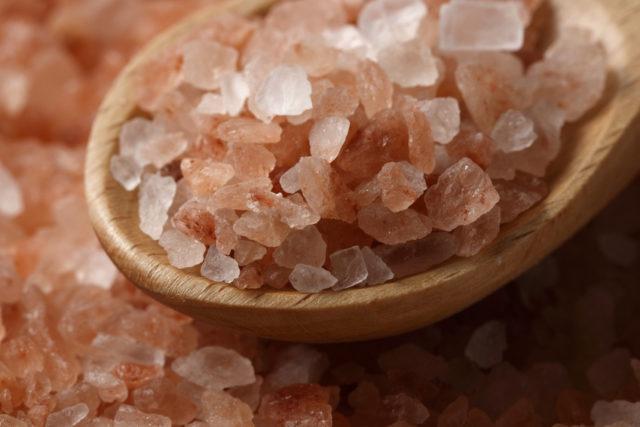 ピンク色の岩塩を木のスプーンですくっている写真