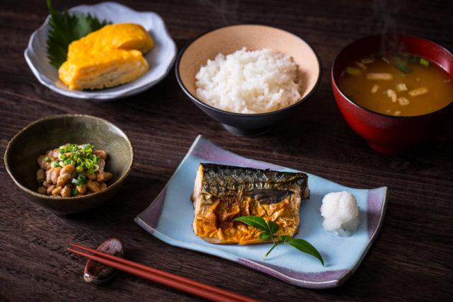 ごはん、みそ汁、納豆、だし巻き卵、焼き魚を置かれた食卓の写真