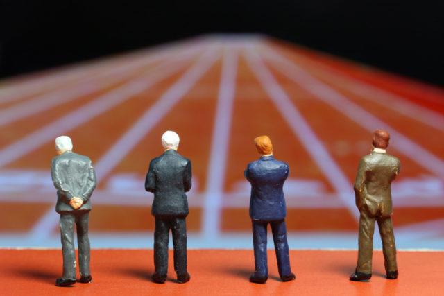 ビジネスマンを模した人形がスタートラインに立っている写真