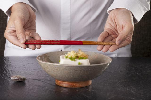 焼き物の器に豆腐が盛り付けられ、その後ろで赤いお箸を水平に持っている写真