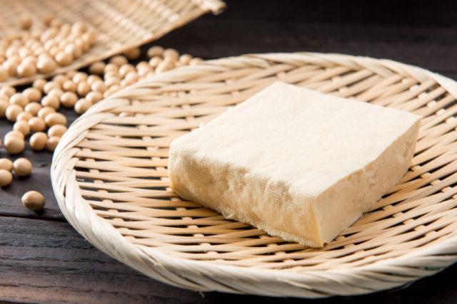 ざるの上に木綿豆腐が置かれており、後ろには大豆が置かれている写真