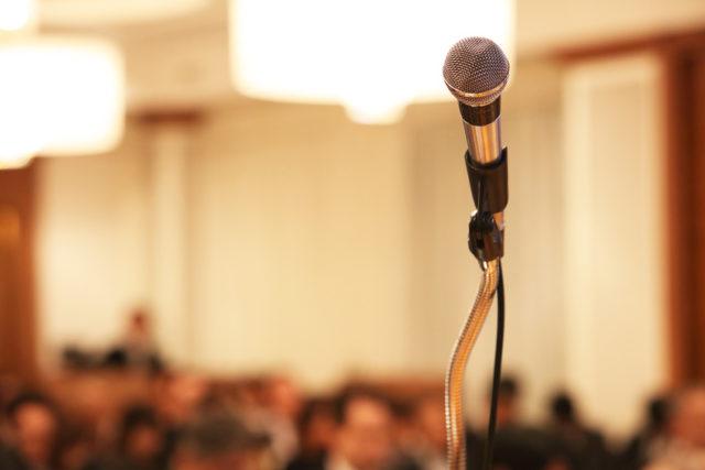 講演会のマイクがクローズアップされた写真