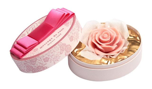 ピンク色の大きなリボンがついた楕円形の箱の中にバラの形のチョコレートが入っている写真