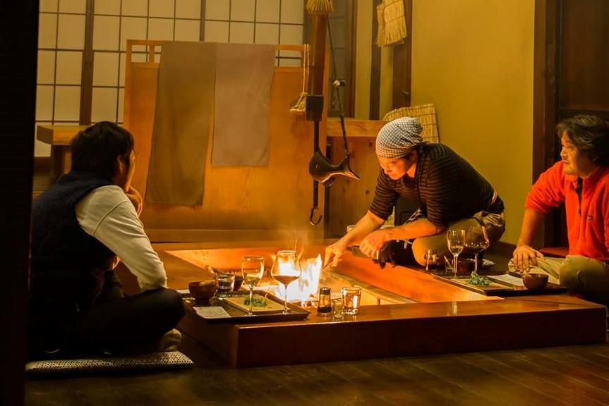 男性3人が囲炉裏を囲って座っている写真