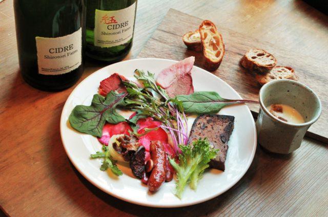 ワインボトルと、丸皿に肉料理が盛り付けられ、日のさらにバゲットが盛り付けられている写真