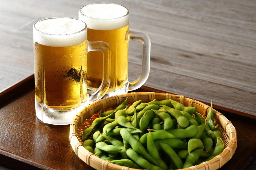 茶色いお盆の上にビールとかごに入った枝豆が置かれている写真