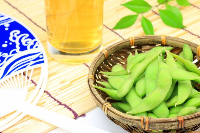 かごに盛り付けられた枝豆とビールとうちわの写された写真