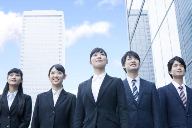 ビル街の中に男女5人の新社会人が並んで立っている写真