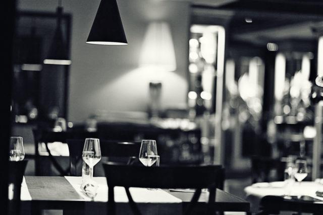 テーブルにワイングラスが置かれたモノクロの写真