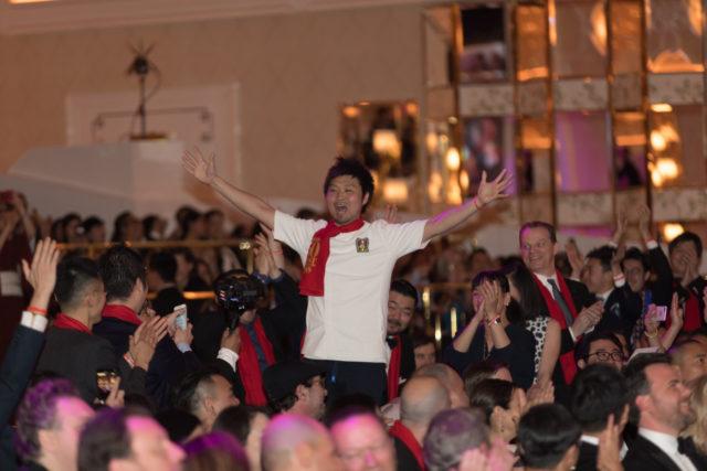 両手を広げて立ち上がっているTシャツ姿の男性の写真