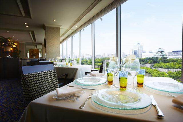 窓際のテーブルに食器がセッティングされている写真