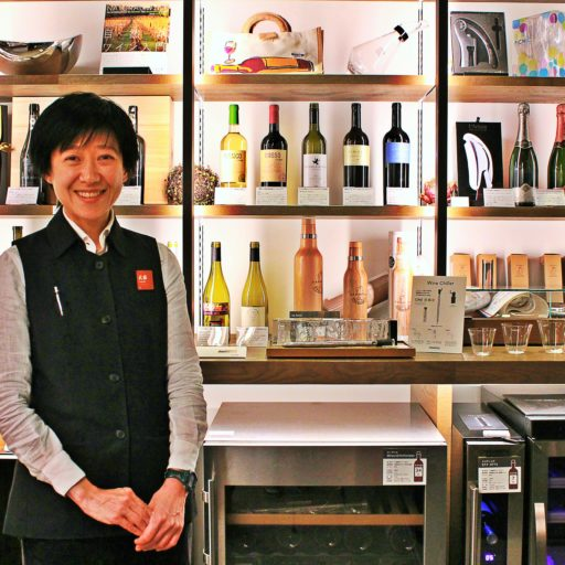 さまざまな商品がディスプレイされた棚の前でコンシェルジュの女性がたたずんでいる写真