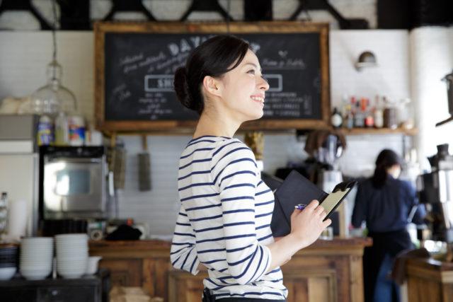 カフェの店内でボーダーのシャツを着た女性が伝票を手に微笑んでいる写真