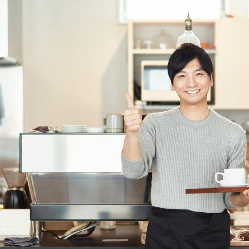 カフェの店内でコーヒーカップが乗ったお盆を持った男性が笑顔で立っている写真