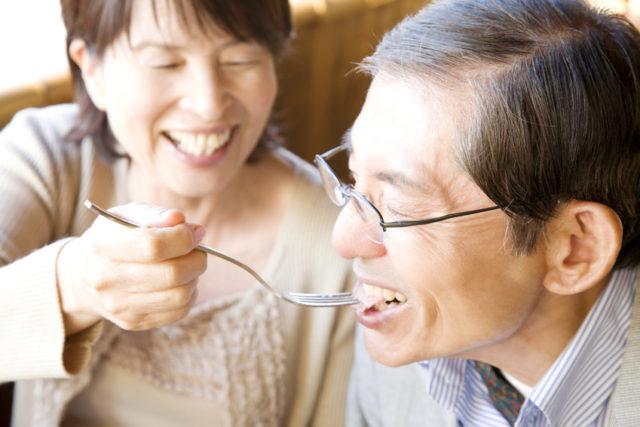 老夫婦が笑顔で食事をしている写真
