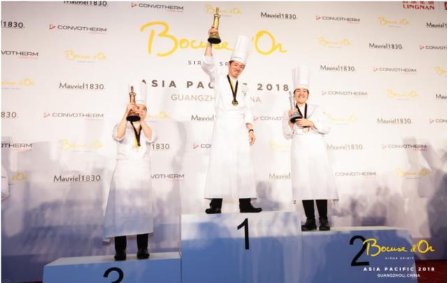 表彰台の上にコック姿でトロフィーを掲げた3人が立っている写真