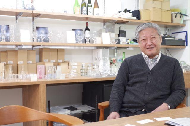 グラスがたくさん置かれた棚の前に座る木本社長の写真
