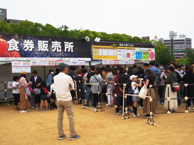 食券販売所の前に行列ができている様子の写真