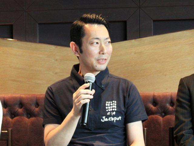 黒いシャツ江沖田大島さんがマイクを持っている写真