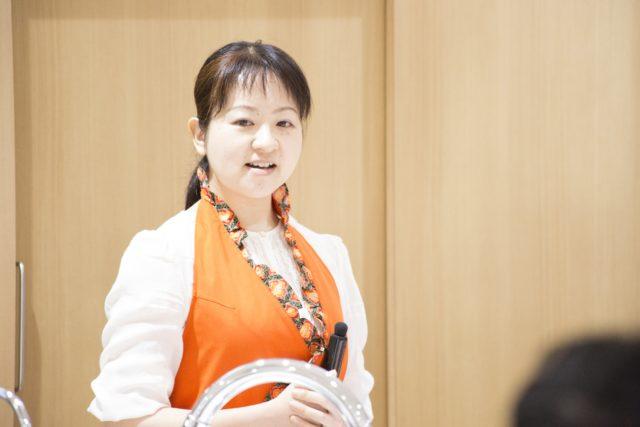 オレンジ色のエプロンをした高山さんの写真