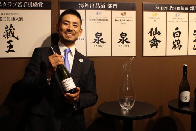Arizona Sake LLCの男性が酒瓶を持っている写真