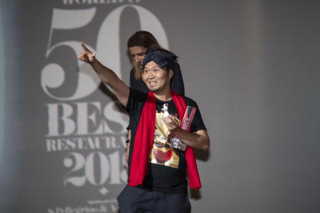 トロフィーを片手に笑顔の長谷川氏の写真