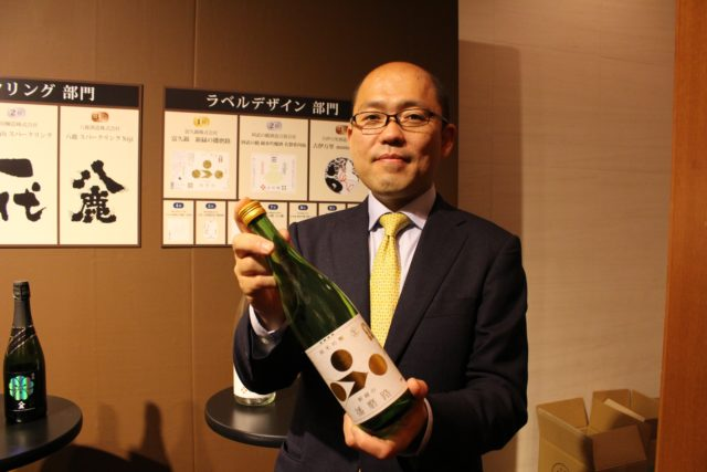 富久錦株式会社の男性が酒瓶を持っている写真