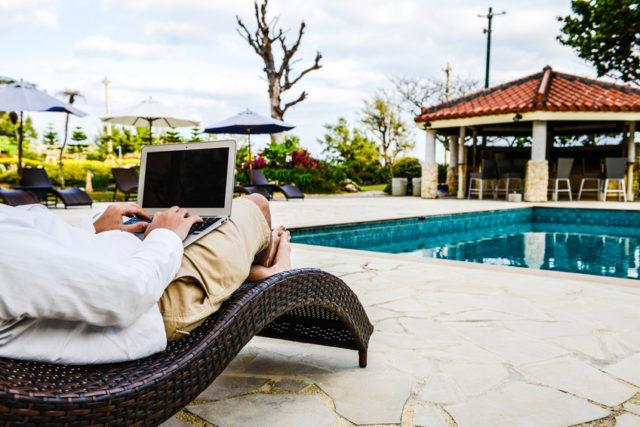 プールサイドでパソコンを操作する男性の画像
