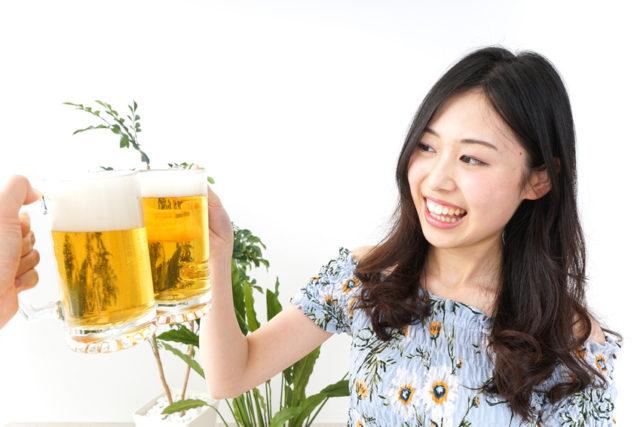 女性がビールジョッキで乾杯している画像