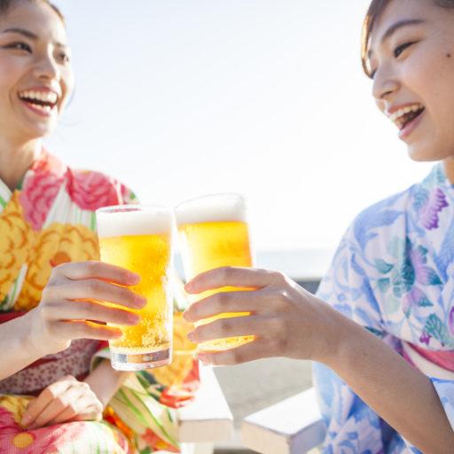 浴衣を着た女性たちは美味しそうにビールを飲んでいる画像