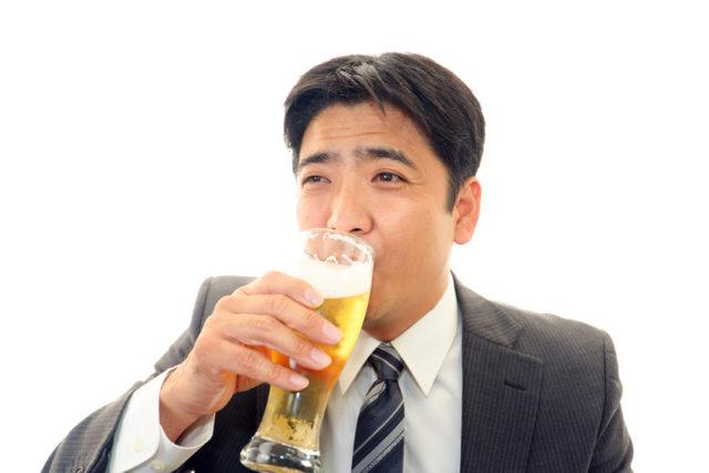 ビールを飲むスーツの男性の画像