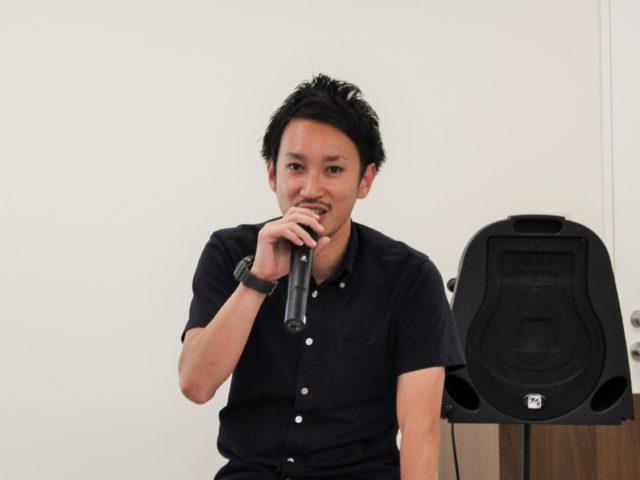 マイクを片手に三浦さんがスピーチをしている写真