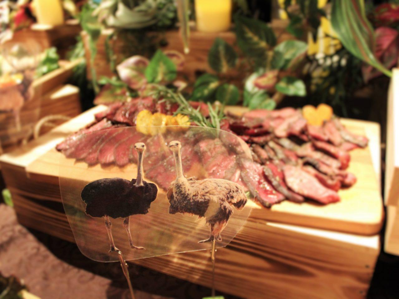木のテーブルの上に肉がのっており、手前にダチョウのオブジェがある写真