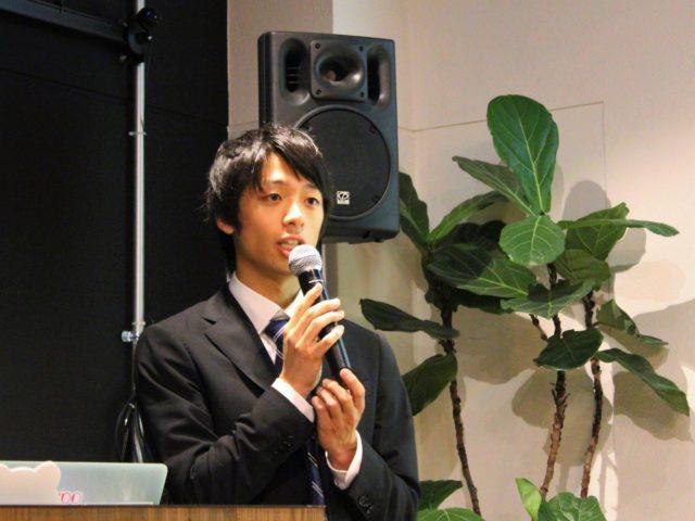 マイクを持つ若いスーツ姿の男性の写真