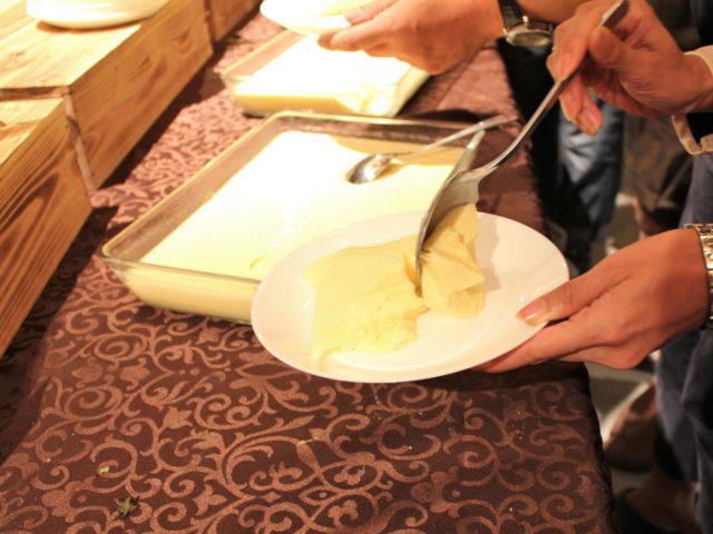 ダチョウの卵で作ったプリンを白い皿に取り分けている写真