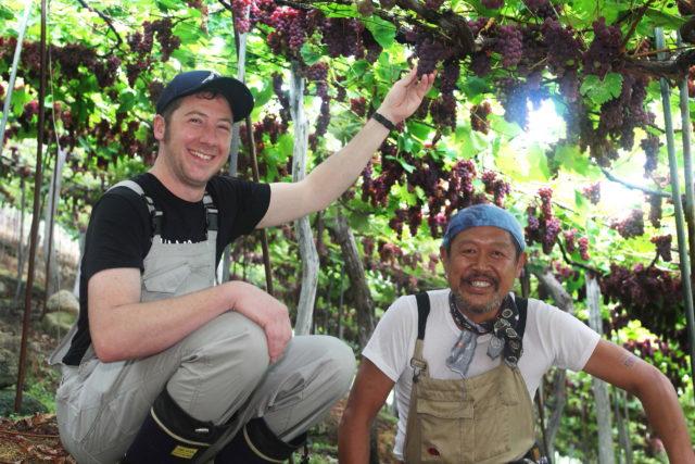 アレックス・クレイグヘッド氏と藤巻氏が笑顔でブドウの木の下でしゃがんでいる写真