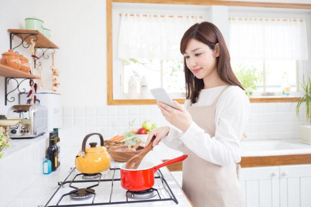 スマートフォンを見て料理をする女性の画像