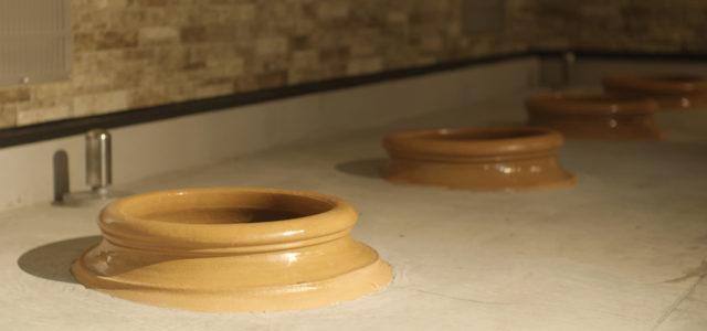 陶器の壺を土中に埋めて、その中にブドウを入れて自然発酵させている様子の写真