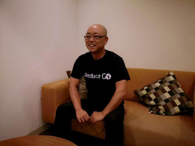 ソファーに腰掛けた坊主にめがね姿の上村さんの写真