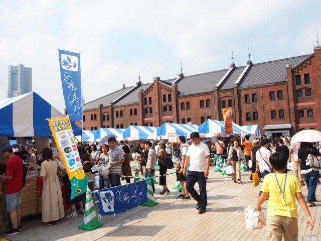 レンガ倉庫と青と白のパラソルやテントが連なっている会場の様子の写真