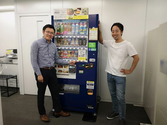 ぐるなび社内に設置されている自販機の前で野村さんと樋口さんが立っている写真