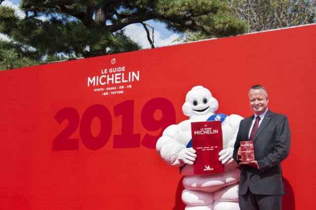 ミシュランマンと日本ミシュランタイヤ株式会社 代表取締役社長のポール・ペリニオさんがパネルの前で立っている写真
