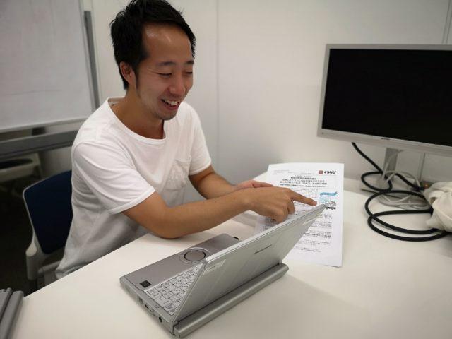 パソコンを開いて資料を片手に説明している野村さんの写真