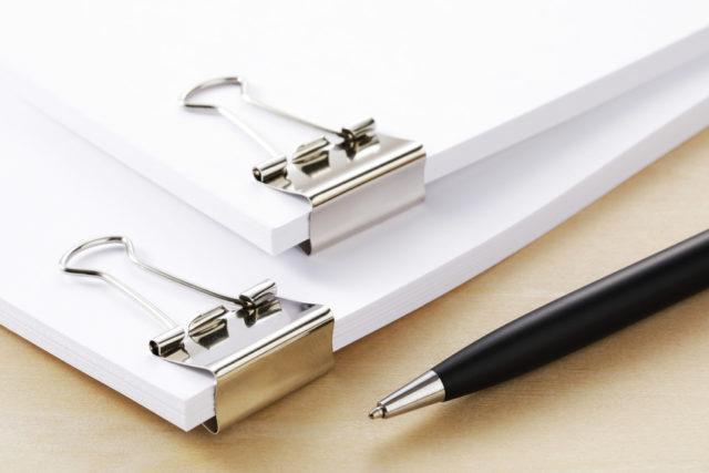 神をクリップで挟みそのそばにペンが置かれている画像
