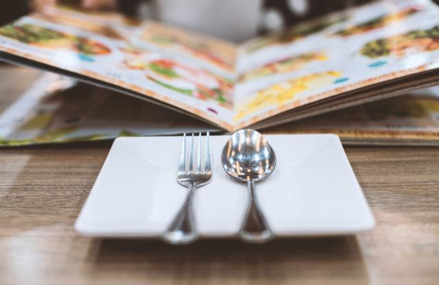 スポーンとフォークが皿の上に置かれ、奥でメニューが開かれている画像