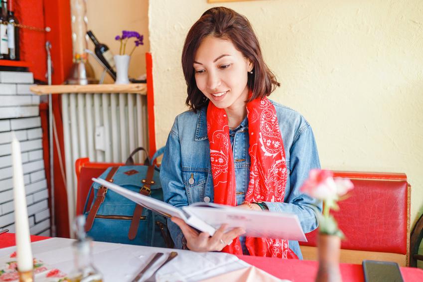メニューを手に持ち料理を選んでいる様子の女性の画像