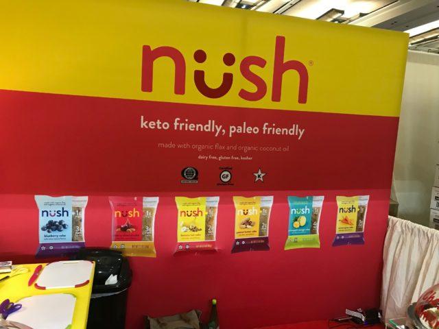 nushと書かれた赤と黄色の壁に商品が描かれている写真