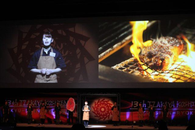 「Beer&wine 石山GRILL」のスタッフと熟成肉が焼かれている様子がスクリーンに映し出されている