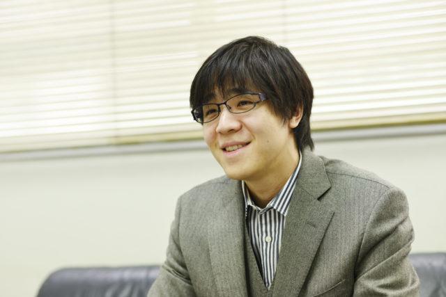 笑顔で受け答えをする古田氏の写真