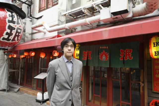 お店の前に立っている古田氏の写真